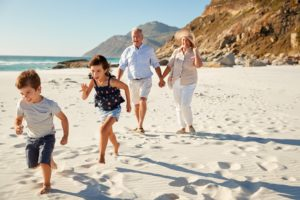 Senior white couple and their grandchildren walking on a sunny beach, close up