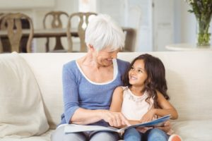 Grandmother and granddaughter interacting while looking at photo album in living room